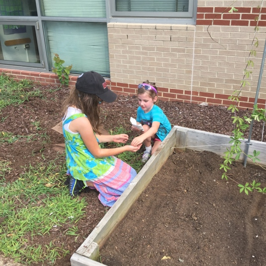 Forest View alum Sarah (2013) plants with rising kindergartener Lilian