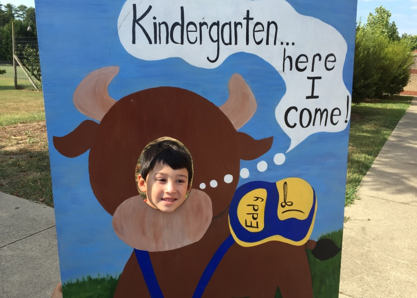Kindergartener poses with DPS sign